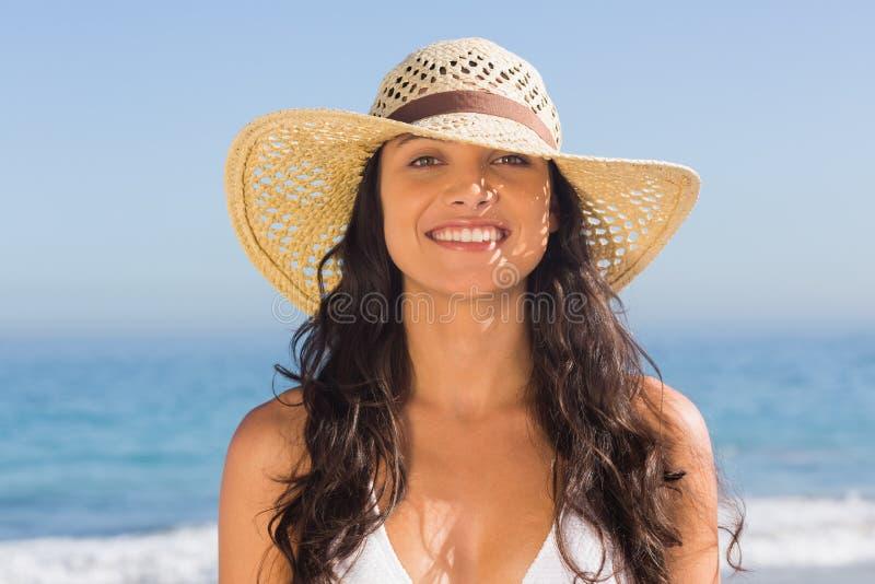 Lächelnde tragende Strohhutaufstellung der attraktiven dunkelhaarigen Frau lizenzfreies stockbild