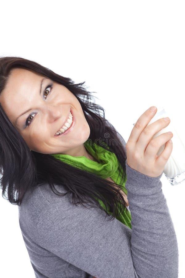 Lächelnde Trinkmilch der Brunettefrau über Weiß stockbild