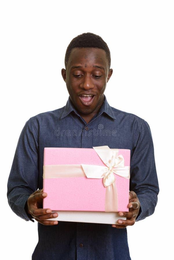 Lächelnde und öffnende Geschenkbox des jungen glücklichen afrikanischen Mannes stockbilder