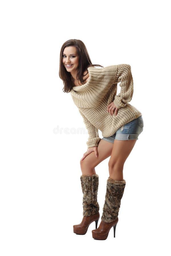 Lächelnde und aufwerfende Brunettefrau stockfoto