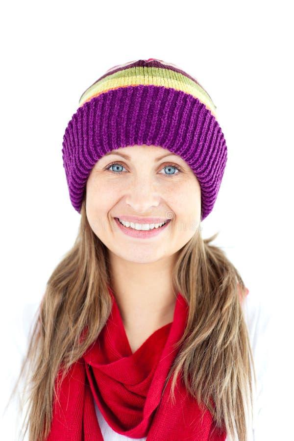 Lächelnde und tragende Schutzkappe der lustigen Frau und roter Schal stockfoto