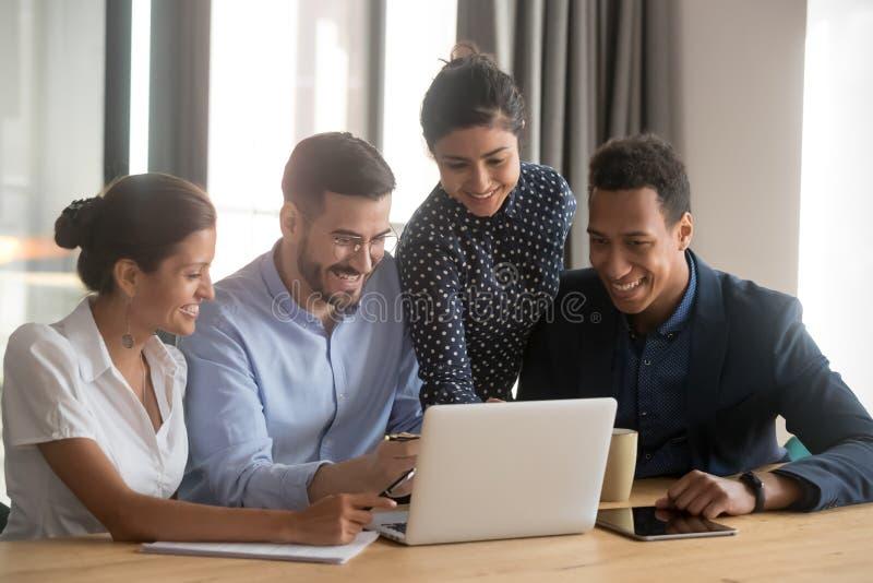 L?chelnde verschiedene Angestellte lachen das Zusammenarbeiten ?ber Laptop beim B?ro stockfotografie