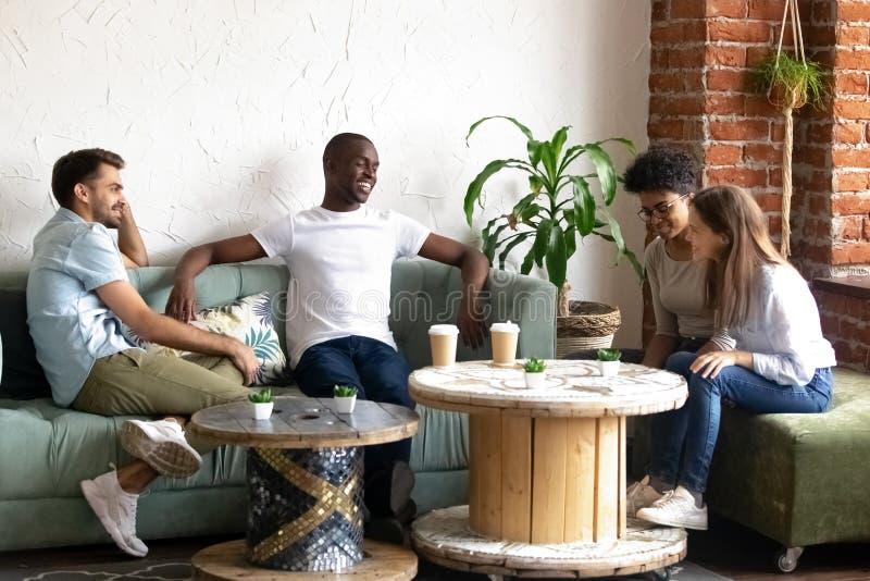 Lächelnde verschiedene junge Leute erhalten im Café bekannt gemacht stockfoto