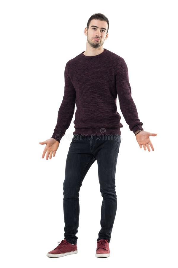 Lächelnde verwirrte tragende kastanienbraune Strickjacke des Mannes mit den verbreiteten Armen, die oben schauen lizenzfreies stockfoto