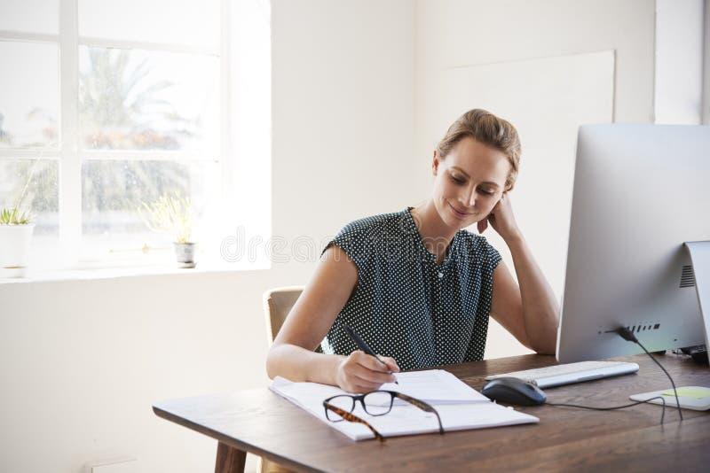 Lächelnde weiße Frau, die in einem Büro macht Anmerkungen arbeitet lizenzfreie stockbilder