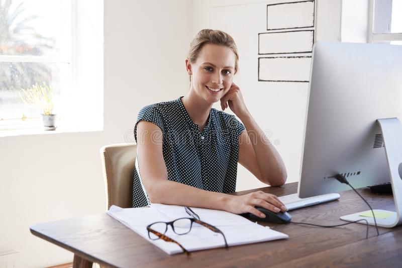 Lächelnde weiße Frau, die in einem Büro schaut zur Kamera arbeitet lizenzfreies stockfoto
