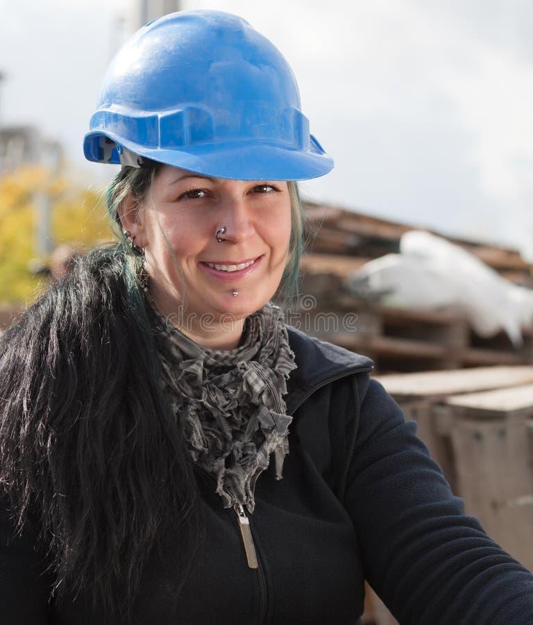 Lächelnde weibliche Arbeitskraft im blauen harten Hut stockfotografie