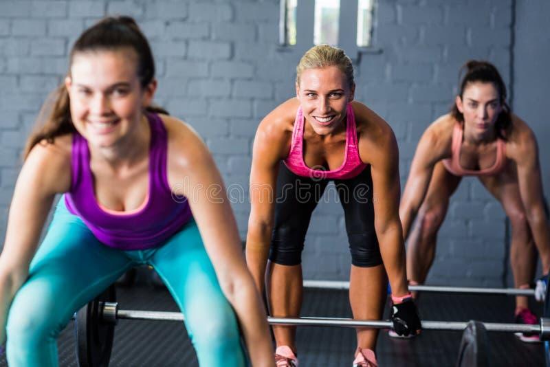 Lächelnde weibliche Athleten, die Barbells anheben stockfotos