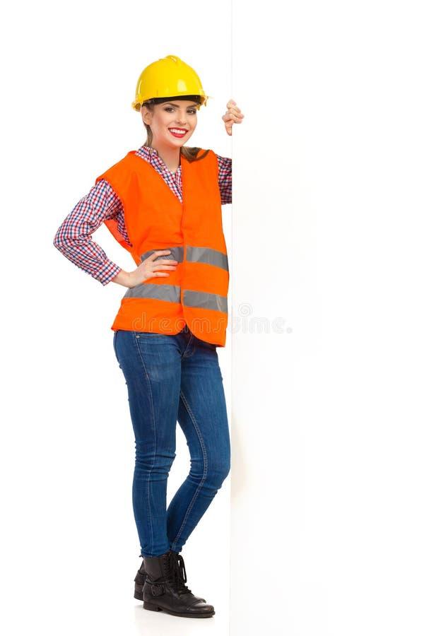 Lächelnde Weibliche Bauarbeiter-Standing Close To-Weiß-Fahne ...