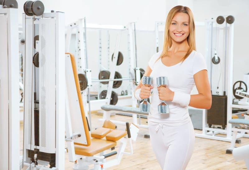 Lächelnde weibliche haltene Gewichte des Sports stockbilder