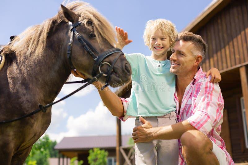 Lächelnde Weile des Sohns, die zum ersten Mal Pferd berührt stockbild