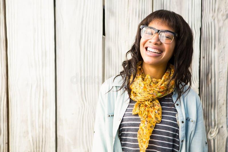 Lächelnde zufällige Frau, die mit Gläsern aufwirft lizenzfreie stockbilder