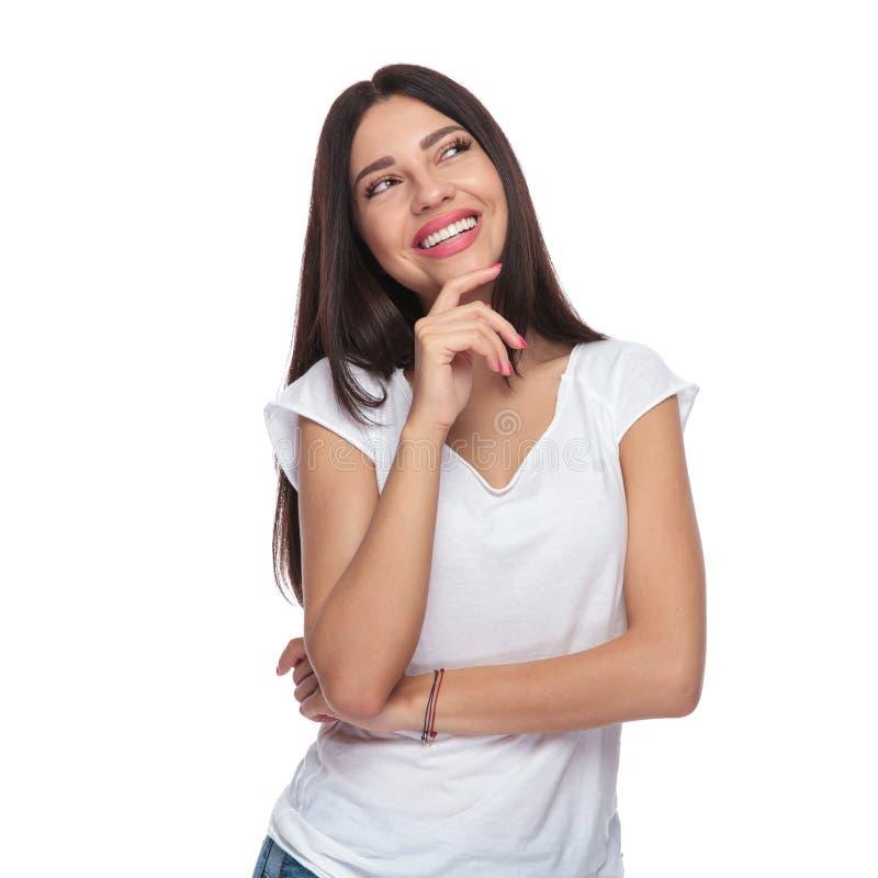 Lächelnde zufällige Frau, die oben schaut, um beim Denken mit Seiten zu versehen lizenzfreie stockbilder