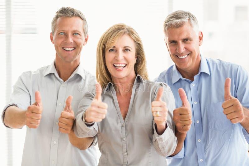 Lächelnde zufällige Geschäftsleute, die oben Daumen tun lizenzfreies stockfoto