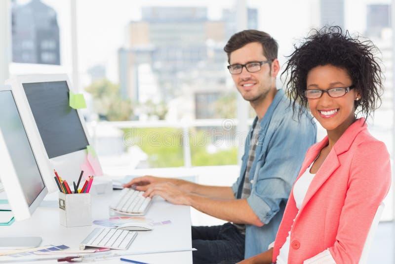 Lächelnde zufällige junge Paare, die an Computern arbeiten lizenzfreie stockbilder