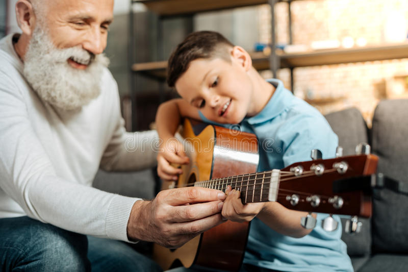 Lächelndem Großvater, enkel zeigend, wie man Gitarre spielt lizenzfreie stockfotografie