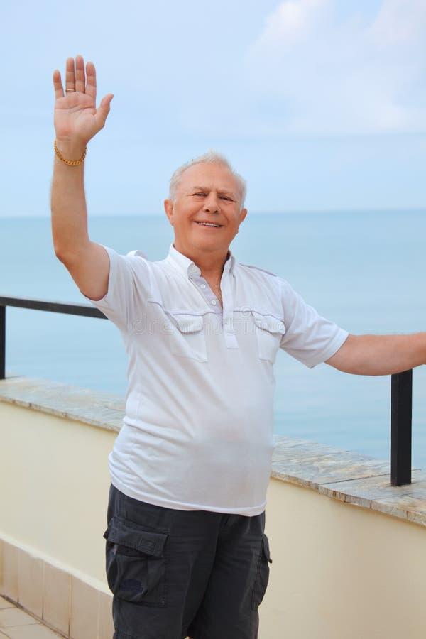 Lächelnder Älterer auf Veranda nahe Seeküste lizenzfreie stockfotos