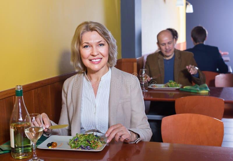 Lächelnder älterer Kunde mit Lebensmittel und Wein stockfotos