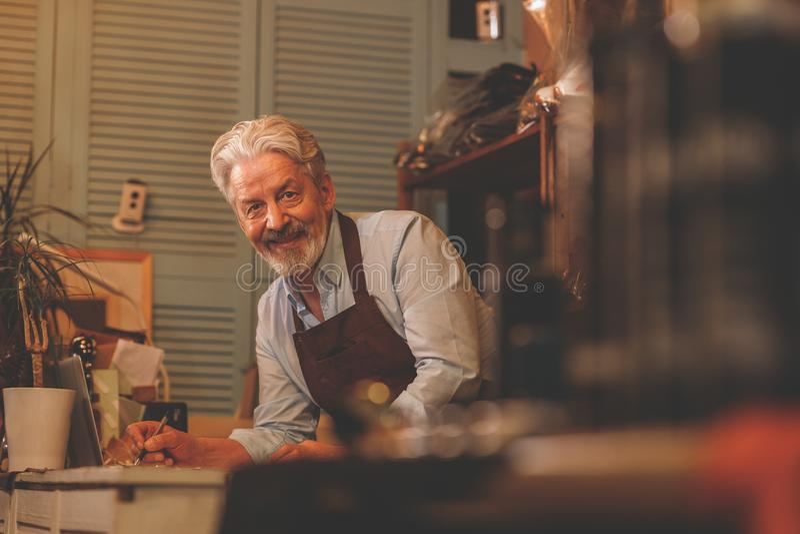 Lächelnder älterer Mann bei der Arbeit lizenzfreie stockbilder