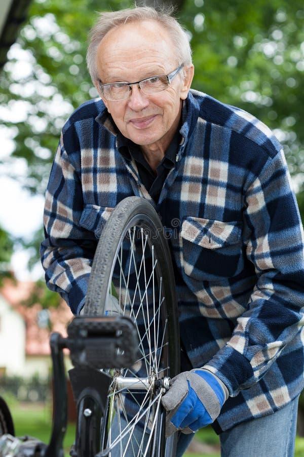 Lächelnder älterer Mann, der ein Fahrrad repariert lizenzfreie stockbilder