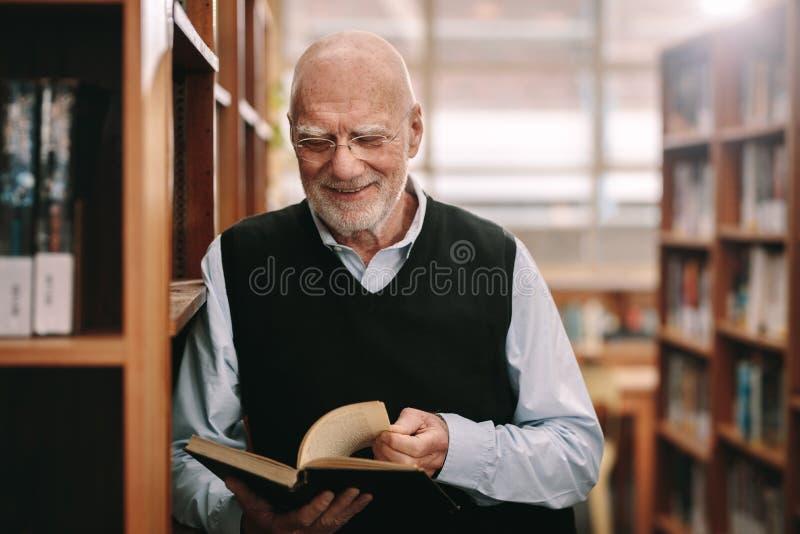 Lächelnder älterer Mann, der eine Buchstellung in einer Bibliothek betrachtet stockfoto