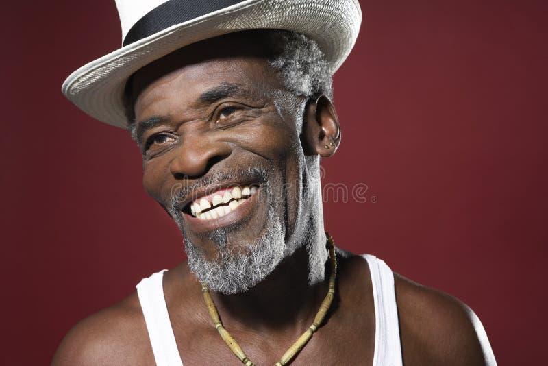 Lächelnder älterer Mann, der Fedora trägt stockfotos