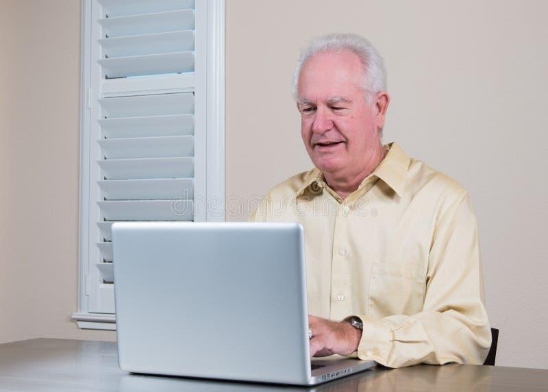 Lächelnder älterer Mann, der an Laptop arbeitet stockbilder