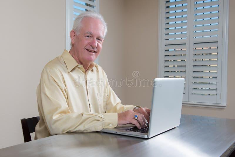 Lächelnder älterer Mann, der an Laptop arbeitet lizenzfreies stockfoto
