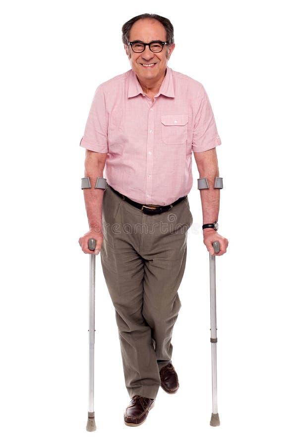 Lächelnder älterer Mann, der mit zwei Krückeen geht stockfotos