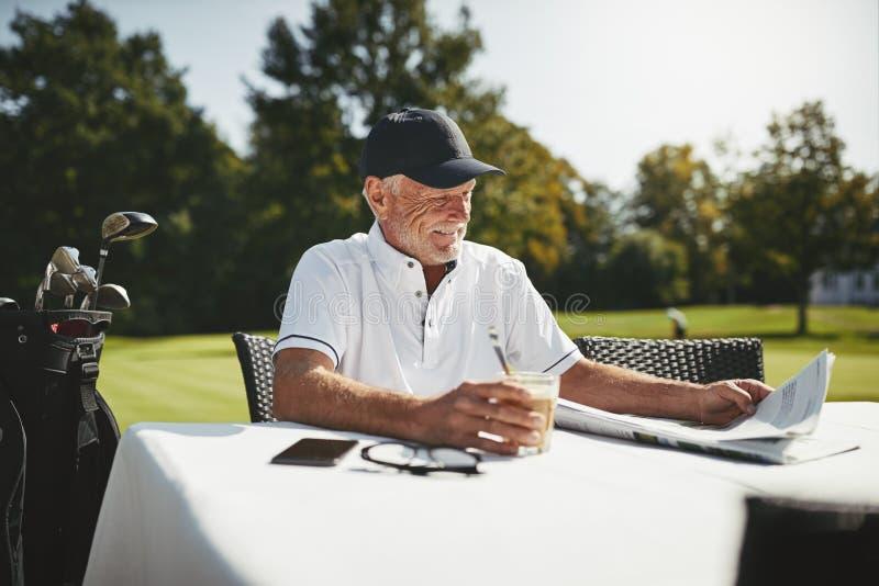 Lächelnder älterer Mann, der nachdem eine Golf-Runde sich entspannt, gespielt worden ist lizenzfreies stockbild