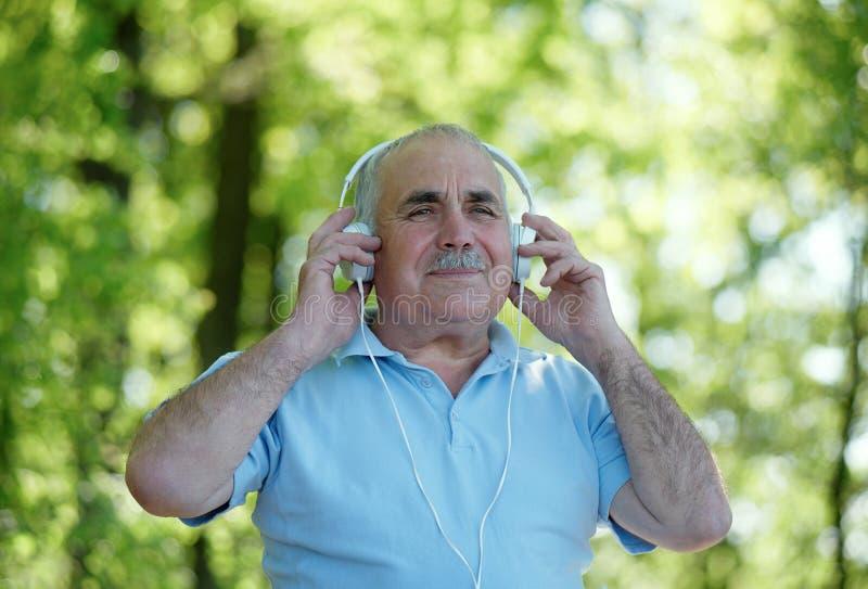 Lächelnder älterer Mann, der seine Musik genießt stockbild