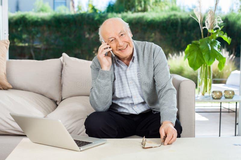 Lächelnder älterer Mann, der Smartphone an der Krankenpflege beantwortet lizenzfreie stockfotografie