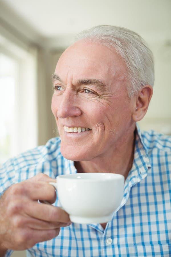 Lächelnder älterer Mann, der Tasse Kaffee im Wohnzimmer hat lizenzfreie stockfotos
