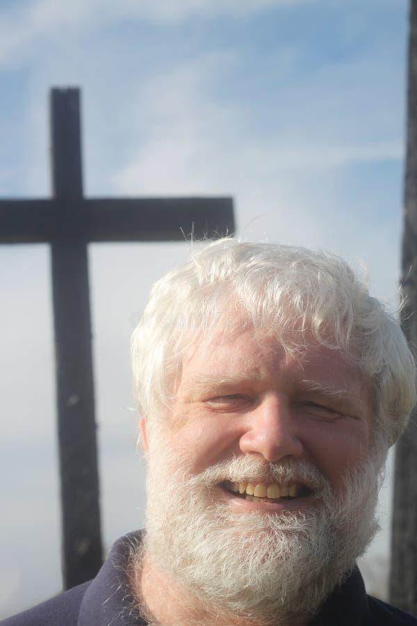Älterer Mann vor einem Kreuz stockfotos
