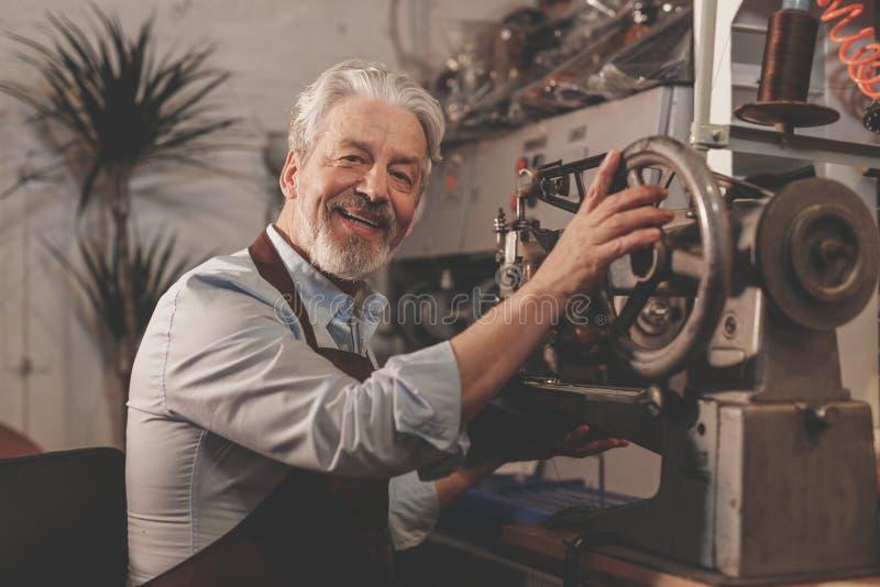 Lächelnder älterer Mann in einer Werkstatt lizenzfreie stockfotos