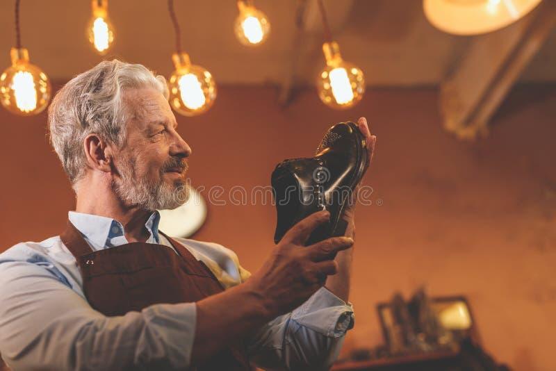 Lächelnder älterer Mann mit einem Schuh stockfotos