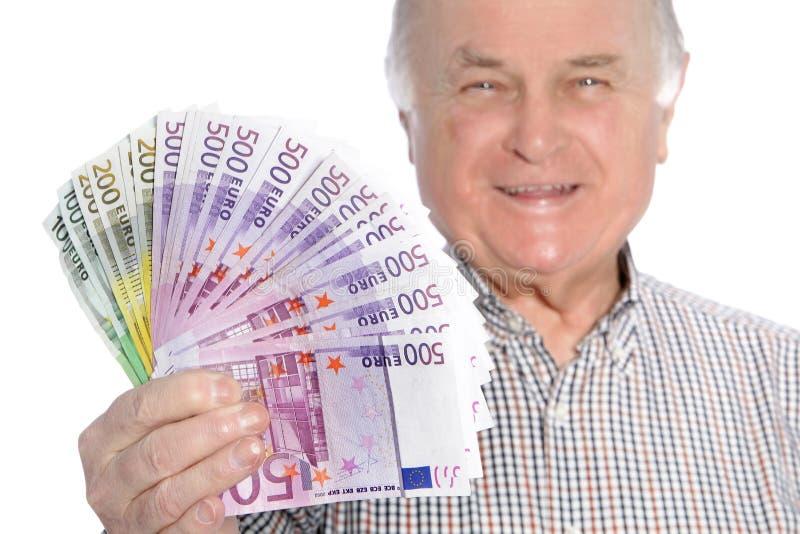 Lächelnder älterer Mann mit einer Handvoll Geld stockfotos