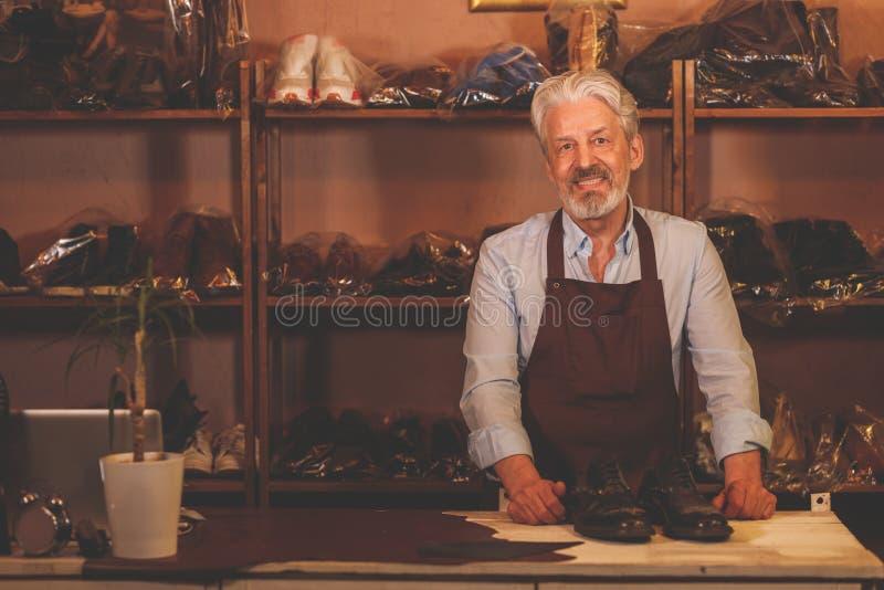 Lächelnder älterer Mann am Zähler stockbild