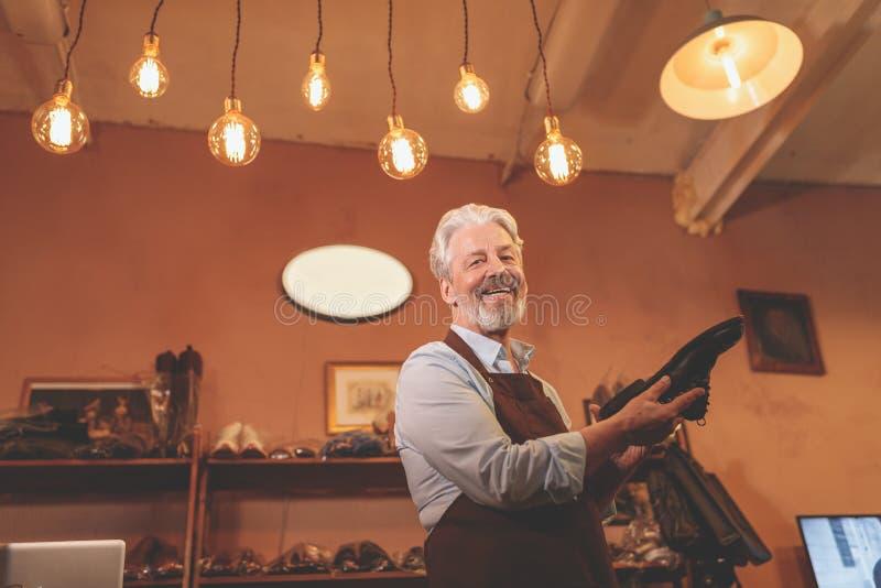 Lächelnder älterer Schuster mit einem Schuh stockfotografie