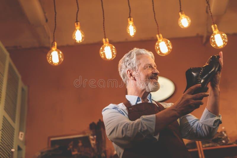 Lächelnder älterer Schuster mit einem Schuh stockfoto