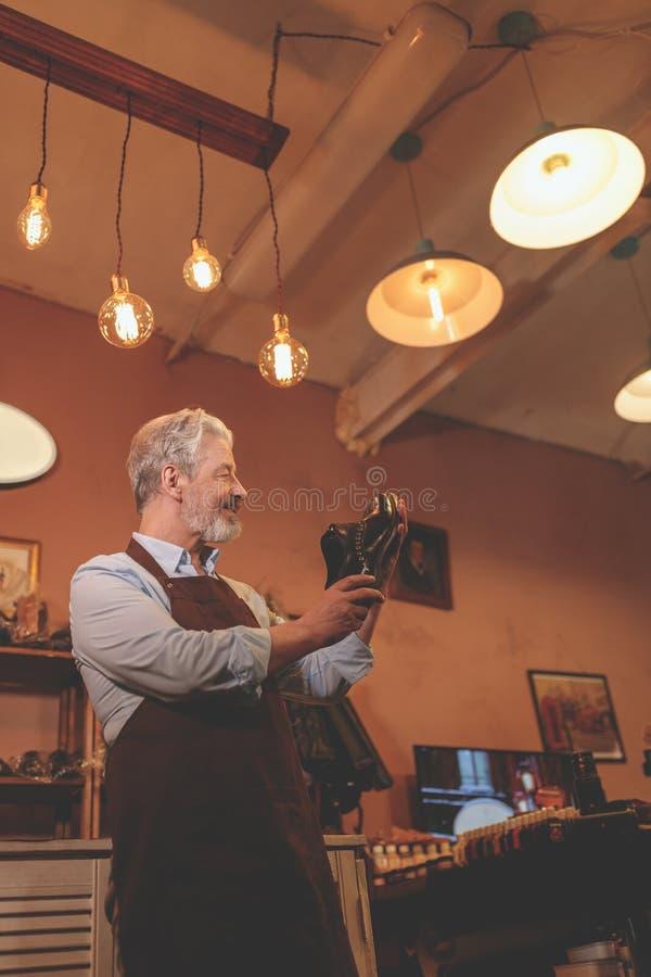 Lächelnder älterer Schuster mit einem Schuh lizenzfreie stockfotografie