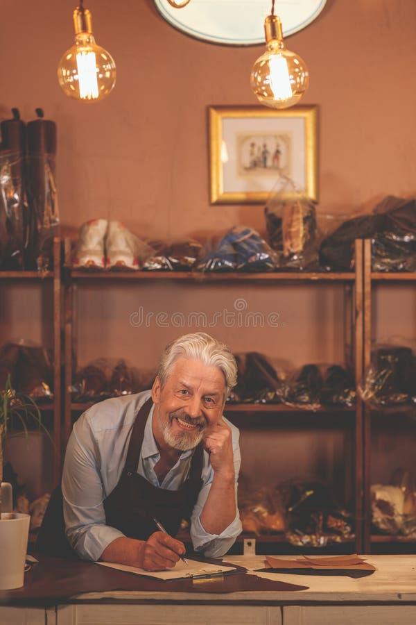 Lächelnder älterer Schuster zuhause lizenzfreies stockfoto