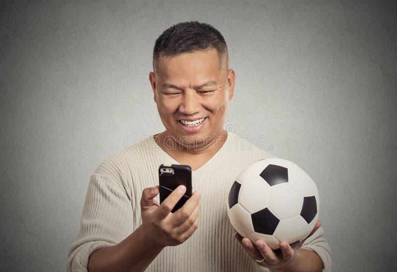 Lächelnder überraschter Mann, der auf dem aufpassenden Spiel des Smartphone hält Fußball schaut lizenzfreie stockbilder