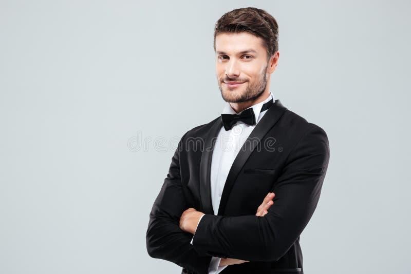 Lächelnder überzeugter Mann im Smoking, das mit den Armen gekreuzt steht stockfoto
