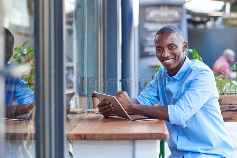 Lächelnder afrikanischer Mann, der online an einem Straßencafézähler arbeitet lizenzfreie stockbilder