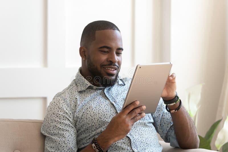 Lächelnder afrikanischer Mann unter Verwendung des digitalen Tablettenlesungs-eBook zu Hause stockbild