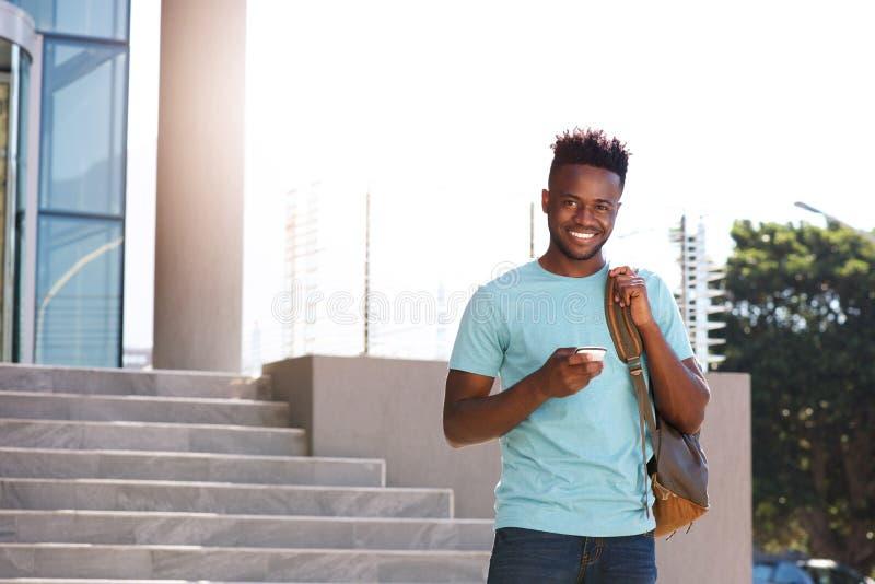 Lächelnder afrikanischer Student, der auf dem Campus Mobiltelefon und Tasche hält stockbild