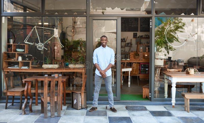 Lächelnder afrikanischer Unternehmer, der Begrüßungs- vor seinem Café steht lizenzfreie stockfotografie