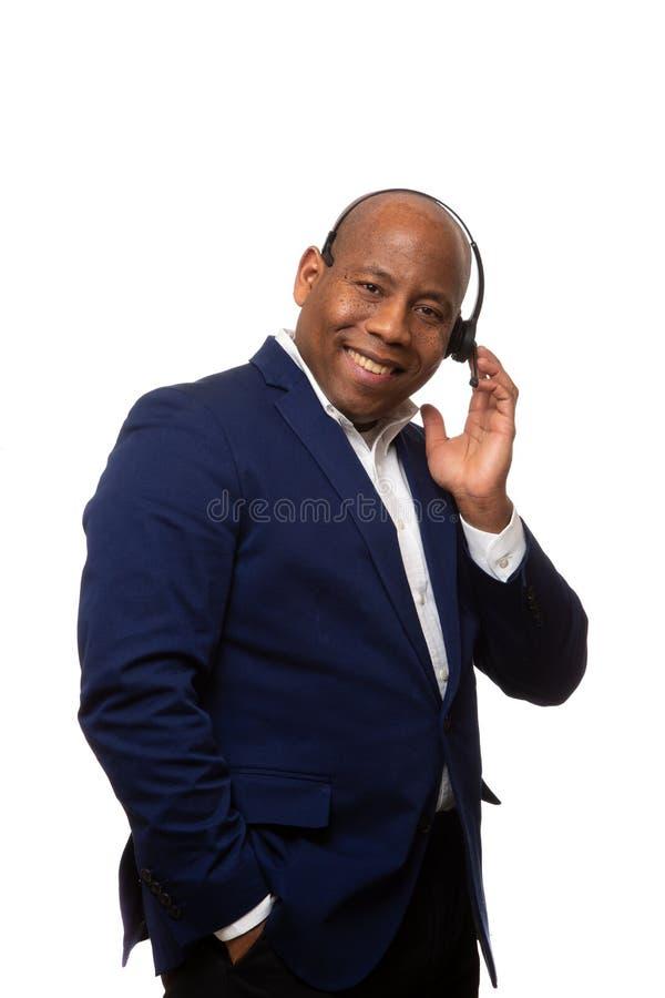 Lächelnder Afroamerikaner-Geschäftsmann Listens Through Headset stockbild
