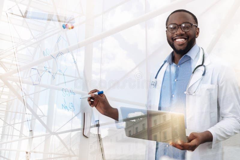 Lächelnder Afroamerikanerdoktor, der Laptop verwenden und Brett lizenzfreies stockfoto
